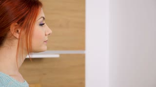 Woman walks to the kitchen and opens the blinds to look through them