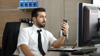 Young attractive businessman having a video conference via his phone at his desk. Talking important business via video chat