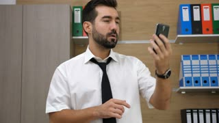 Young attractive businessman having a video conference via his phone. Video chat. Talking important business via video chat