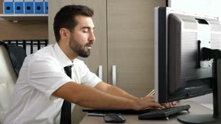 Young attractive businessman relaxing at his desk in the office while putting his legs on the table and watching a video on the PC monitor