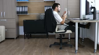 Young business person in the office sliding on the chair while taking notes in papper notebook. Long work hours