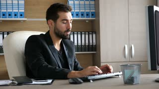 Young businessman at his office typing on the computer. Modern office interior and businessman dressed semi casual