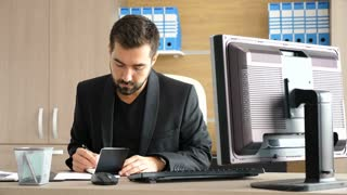 Young businessman in his office taking notes in a paper notebook. Modern business interior. Businessman in dressed semi informal
