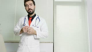 Young doctor in his office talking to the camera. Health care system and medicine