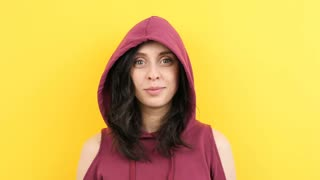 Young hipster woman wearing a hood and making silly faces to the camera on yellow background in studio