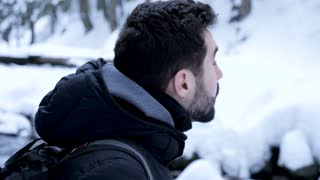 Young man in mountains looking up. Travel in winter