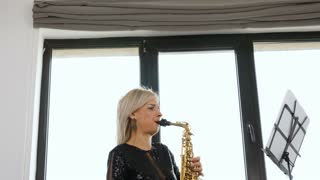 Zoom in of beautiful saxophonist woman playing at the sax in the living room. Jazz player