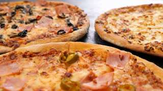Zoom out dolly shot on three pizzas lying on dark wooden table