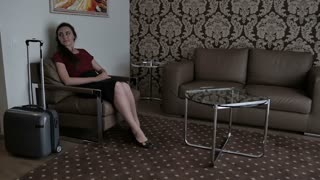 A woman sits in a chair in the hotel room