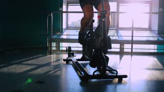 Attractive man in sun rays cycling on the exercise bike in the gym