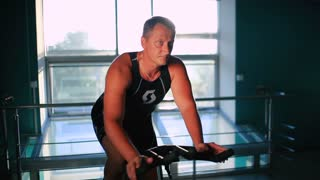Attractive sportsman training on the exercise bike in the gym in sun rays