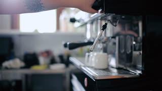 Bartender adds cream to freshly prepared coffee