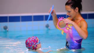 Beautiful mother recreates with her little daughter in the swimming pool