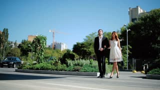 Beautiful woman in white dress and man in black suit are walking on the street