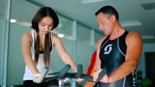 Beautiful young woman training on the exercise bike with trainer in the gym