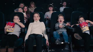 Children are watching the movie in the cinema