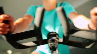 Close-up - man moving the wheel on the exercise bike in the gym