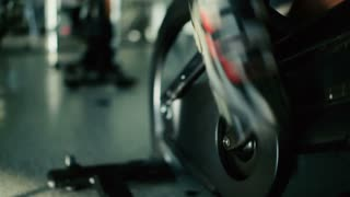 Close-up - man scrolls the pedals on the exercise bike in the gym