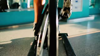 Close-up - the sportsman riding on the exercise bike in the gym