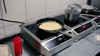 Cook adds an omelet in a pan