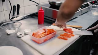 Cook cuts the pieces of red fish