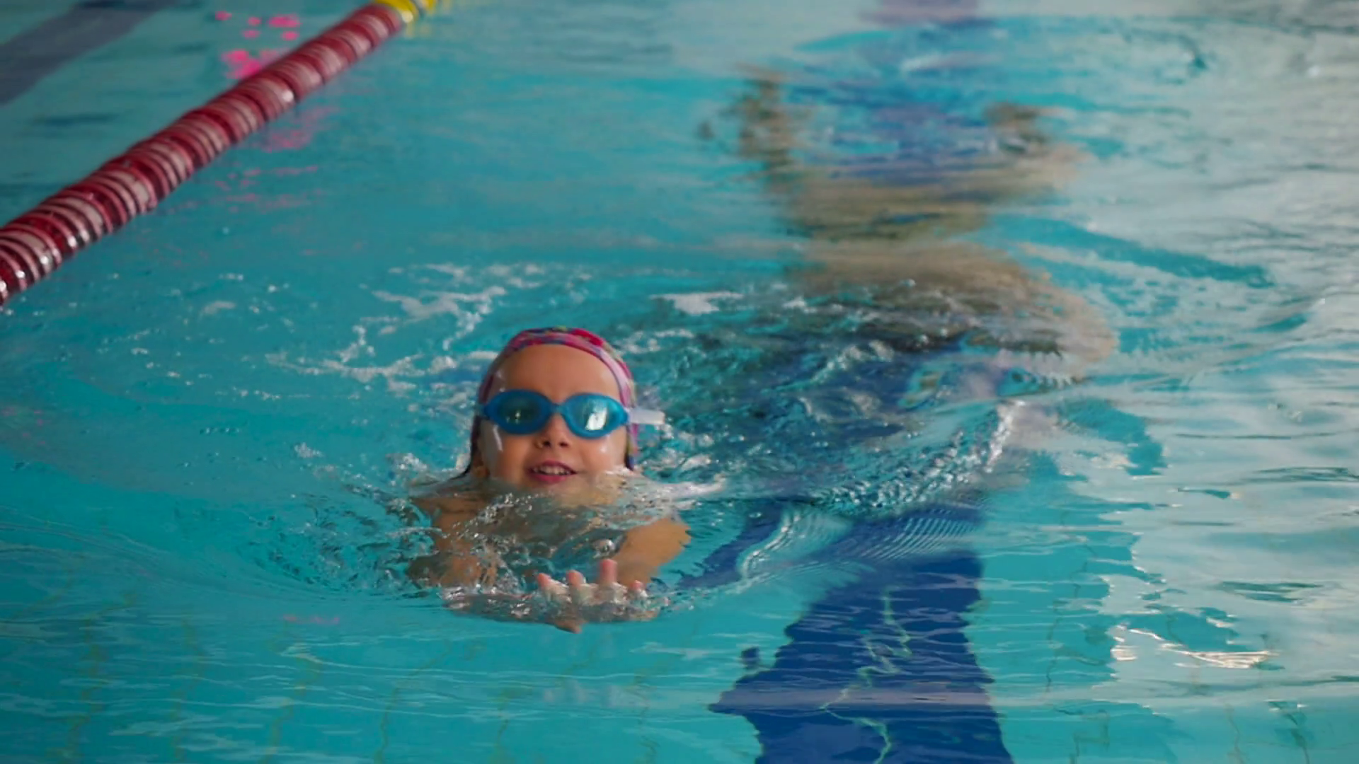 Cute little girl in goggles swimming in the blue pool under the water Stock Video Footage - Storyblocks