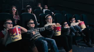 Five boys watch the 3D movie in the cinema