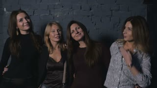 Four attractive women listening a music on a concert