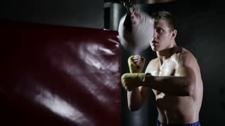 Guy shirtless trains in the boxing hall