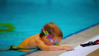 Little boy trying to climb out from the swimming pool