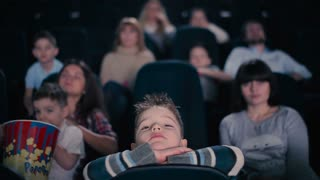 Little boy watch the movie in the cinema