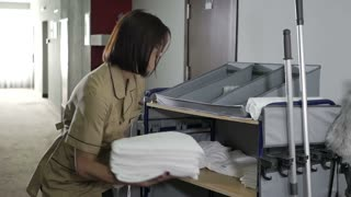 Maid straightens things stand on a rack