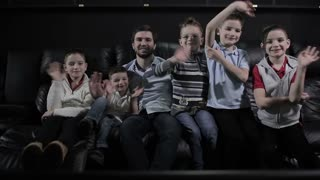 Man and children are waving hands in the cinema