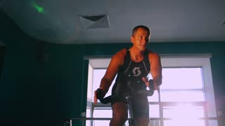 Old attractive sportsman cycling on the exercise bike in sun rays in the gym