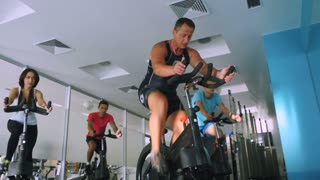 Old trainer training young sportmen the cycling on the exercise bike in the gym