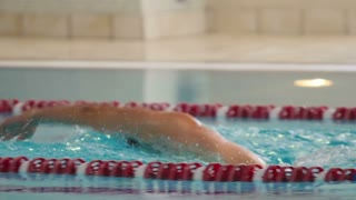 Professional swimmer swimming breaststroke in the blue pool