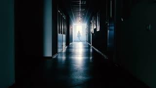 Scientist in protective suit going through dark corridor