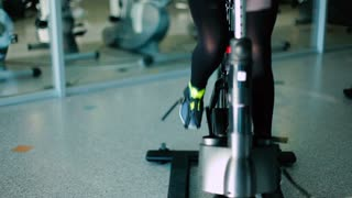 Slim sports legs pedaling on the exercise bike in the gym