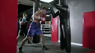 Slow motion training boxers at the boxing bag