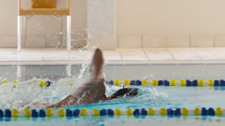 Slowmotion - the sportsman swimming breaststroke in the swimming pool