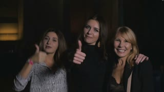 Smiling women show a thumbs into the camera