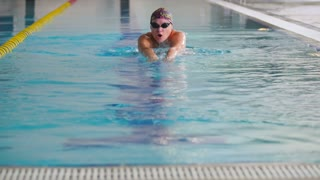 Sports woman in goggles swims under the water in the swimming pool
