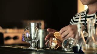 The bartender puts orange slices in a jar
