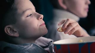 The boy eating the popcorn in the cinema