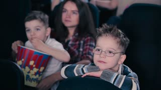 The boy in glasses are watching the movie in the cinema