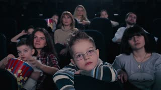 The boy in glasses watch the movie in the cinema