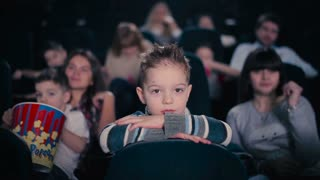 The boy watch the film in the cinema