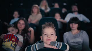 The boy watch the movie in a cinema