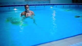 The father teaches his little son to swim in the blue swimming pool