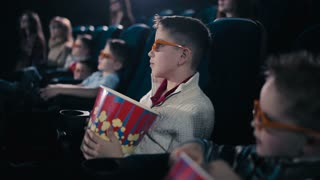 The little boy are smiling in the cinema